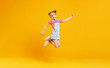 Leinwanddruck Bild - funny child girl jumping on colored yellow background