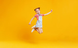 funny child girl jumping on colored yellow background - 208659024