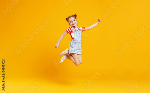 Leinwanddruck Bild funny child girl jumping on colored yellow background