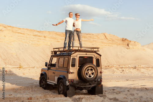 Foto Murales Man and a woman travel by car in the desert.