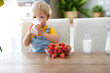 Leinwanddruck Bild - happy baby boy eating strawberries with milk