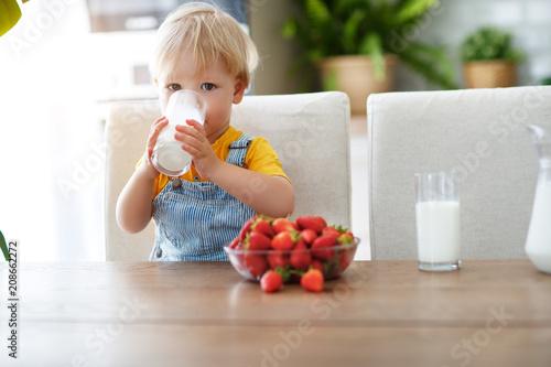 Leinwanddruck Bild happy baby boy eating strawberries with milk