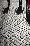 Clear shadows of people on a cobblestone pavement - 208662839