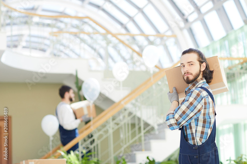 Foto Murales Serious strong handsome young male mover in checkered shirt and overalls carrying cardboard box on shoulder and looking at camera while delivering goods
