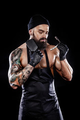 Portrait of bearded barber with a straight razor and comb with tattooe on arm. Barbershop ads concept with copy space.