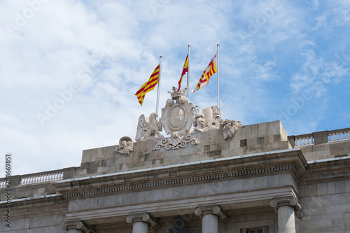 Three flags on top of a building in Barcelona