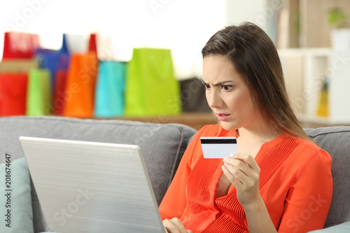 Leinwanddruck Bild Shocked shopper buying online with credit card