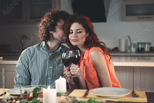 Candlelight dinner. Portrait of relaxed married couple celebrating their anniversary at home. They are drinking wine while sitting at table. Man is hissing woman with love  - 208675092