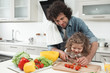 Leinwanddruck Bild - Cheerful girl is watching her daddy cooking. Man is cutting tomatoes on wooden board and smiling. Friendly family concept