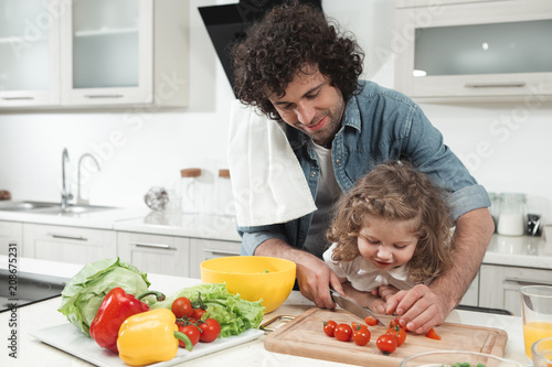Leinwanddruck Bild Cheerful girl is watching her daddy cooking. Man is cutting tomatoes on wooden board and smiling. Friendly family concept