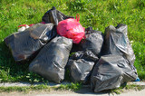 Big bags of garbage in the bright sun. They lay on the green grass. - 208676843