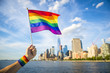 Colorful rainbow gay pride hand flag being waved in the breeze by a man against a sunny city skyline  - 208678034