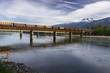 Landscape View of Freight Train Crossing Railway Bridge over Columbia River in Revelstoke, British Columbia Canada
