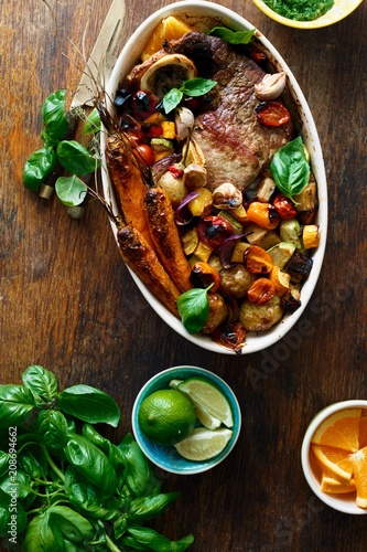 Leinwanddruck Bild Beef meat baked vegetables ceramic pot wooden table top view