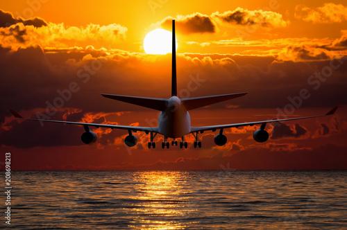 Fototapeta Silhouette of an airplane on sunset