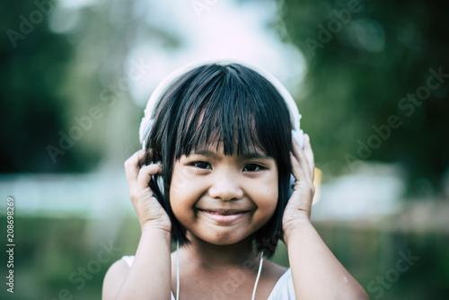 Fotobehang Muziek Little girl listening music in the park