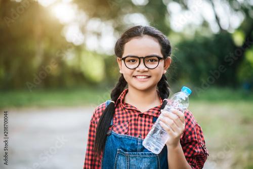 Foto Murales Plastic water bottle in girl hand