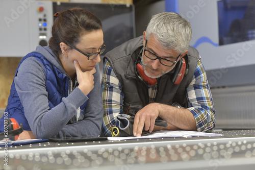 Industrial woodwork technicians reading blueprint - 208707063