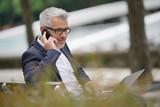 Businessman sitting on public bench talking on phone