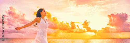 Leinwanddruck Bild - Maridav : Well being free woman with open arms in the air blissful happiness concept banner. Happy woman against pink pastel colorful sunset sky.