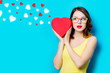 portrait of beautiful young woman with heart shaped box on the wonderful blue studio background with hearts