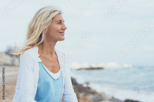 Leinwanddruck Bild Attractive middle-aged blond woman at the seaside