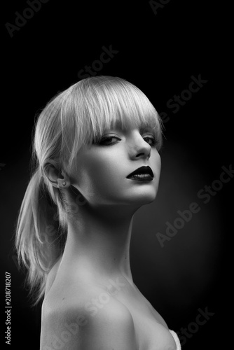 Foto Murales Vertical black and white sideview of young model with evening make up. Girl having beatiful face, plump lips covered with red lipstick, short blonde hair. Posing with opened shoulders.
