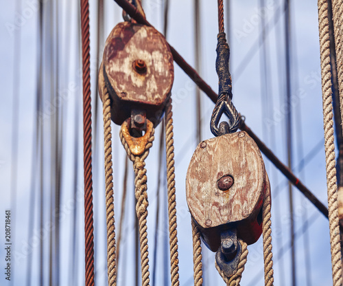 Vintage toned old sailing ship wooden pulleys, nautical background.