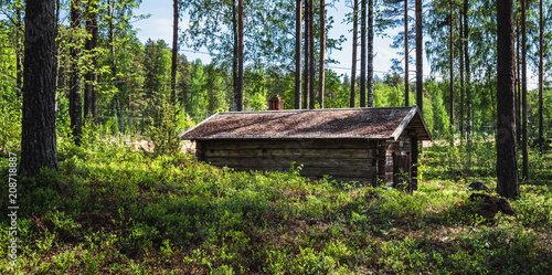 Leinwanddruck Bild Old and idyllic abandoned timber cottage at summer day in Finland