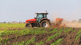 Farmer with tractor seeding - sowing crops at agricultural fields - 208720229