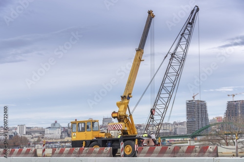 Construction crane truck on the bridge in the city with cloudy sky - 208722400