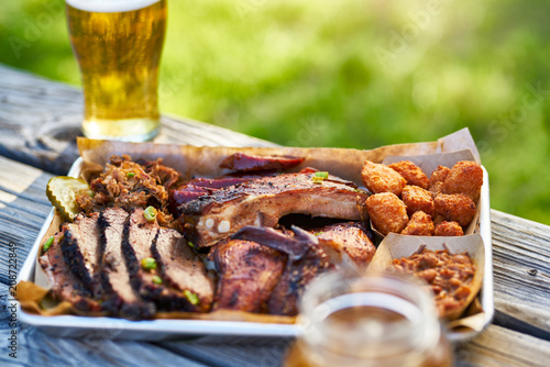 Sticker tray of smoked meats texas bbq style outside on picnic table on sunny summer day