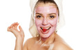 young smiling woman posing with  facial fruit  mask on her face , and with raspberry on her mouth