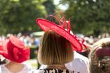 Frau mit rotem Hut auf der Rennbahn