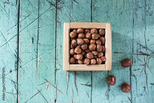 Hazelnuts in wooden box on old cyan table. copy space.