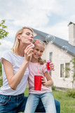 young woman blowing soap bubbles while her daughter sitting near with cup of cola - 208730823