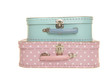 Two kids toy suitcases on each other on a pink background