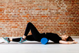 Fitness concept. Beautiful attractive fitness woman with foam roller under back  relaxing after workout on the exercising mat..Portrait of Active Tired Woman Using Blue Foam Roller loft interior. - 208732282