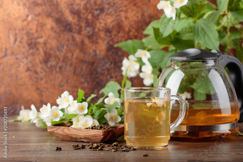Foto Murales Green tea with jasmine in cup and teapot on old wooden table.
