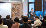 Presenter with Hands Pointing. Blurred De-focused. Unidentifiable Business Audience People Meeting in Conference Room. Speaker in Lecture. MBA Phd Teacher Giving Speech. - 208736615