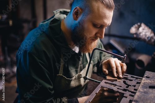 Modern worker performs work with metal, cuts out a detail, jeweler. © Parilov