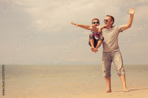 Ojciec i syn gra na plaży w czasie dnia.