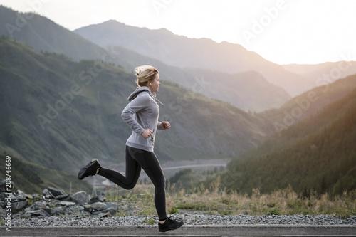 Fototapeta Shot of a beautiful adult woman training at sunrise.