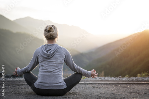 Fototapeta Woman Doing Yoga at sunset. Sports and recreation.