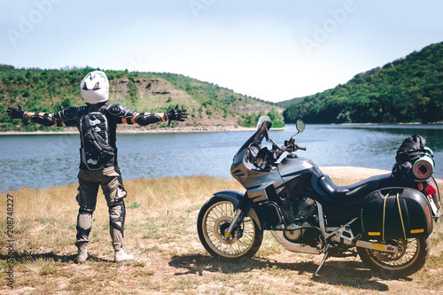 motorcycle driver stands with his arms outstretched. for a meeting of adventures on the dirt beach mountain river, enduro, off road, beautiful view, travel equipment, dual sport, space for text