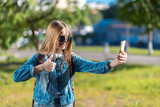 The girl is blonde. A little teenager after school. In summer in park in fresh air. In his hands holds a smartphone. A gesture of hands shows a thumbs up class. Video call with parents on smartphone. - 208749612