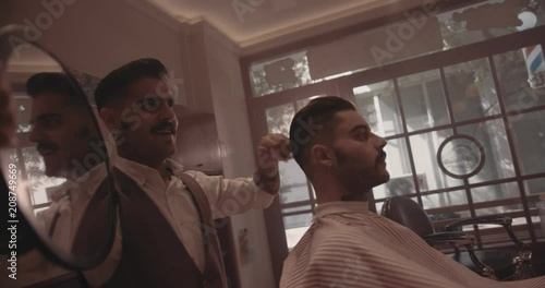 Young stylish barber holding mirror and showing man new haircut