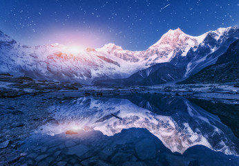 Night scene with himalayan mountains and mountain lake at starry night in Nepal. Landscape with high rocks with snowy peak and sky with stars and moon reflected in water. Moonrise Beautiful Manaslu