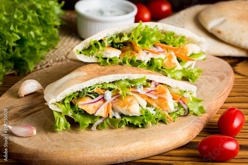 Pita with chicken, vegetables and sauce, delicious lunch, fast food, stuffed roll - 208750638