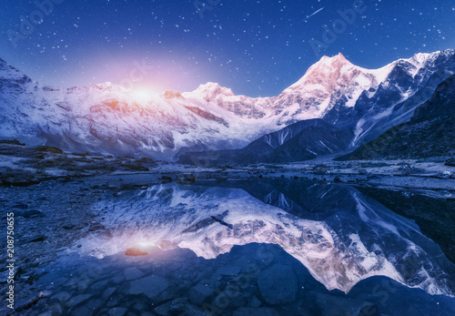 Leinwanddruck Bild Night scene with himalayan mountains and mountain lake at starry night in Nepal. Landscape with high rocks with snowy peak and sky with stars and moon reflected in water. Moonrise Beautiful Manaslu
